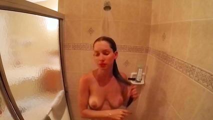 Длинноволосая брюнетка принимает душ