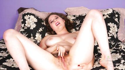 Грудастая рыжая телка мастурбирует волосатую дырочку лежа на кровати