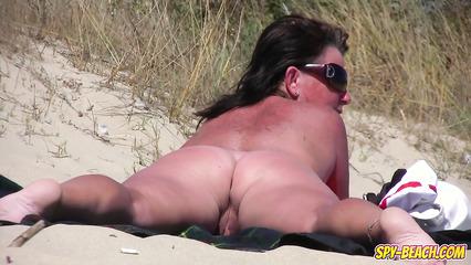 Зрелая нудистка светит потрепанной пилоткой на общественном пляже