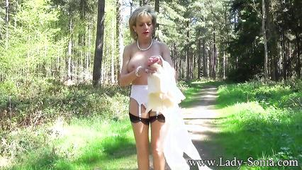 В лесу женщина показывает большие сиськи