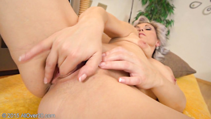 Взрослая блондинка запихивает пальцы в пизденку