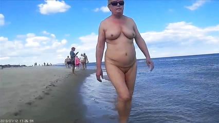 Зрелые бабы гуляют по пляже голыми с похотливыми нудистами