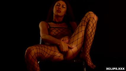 Красавица в сетчатом наряде дрочит нежную киску в темной студии